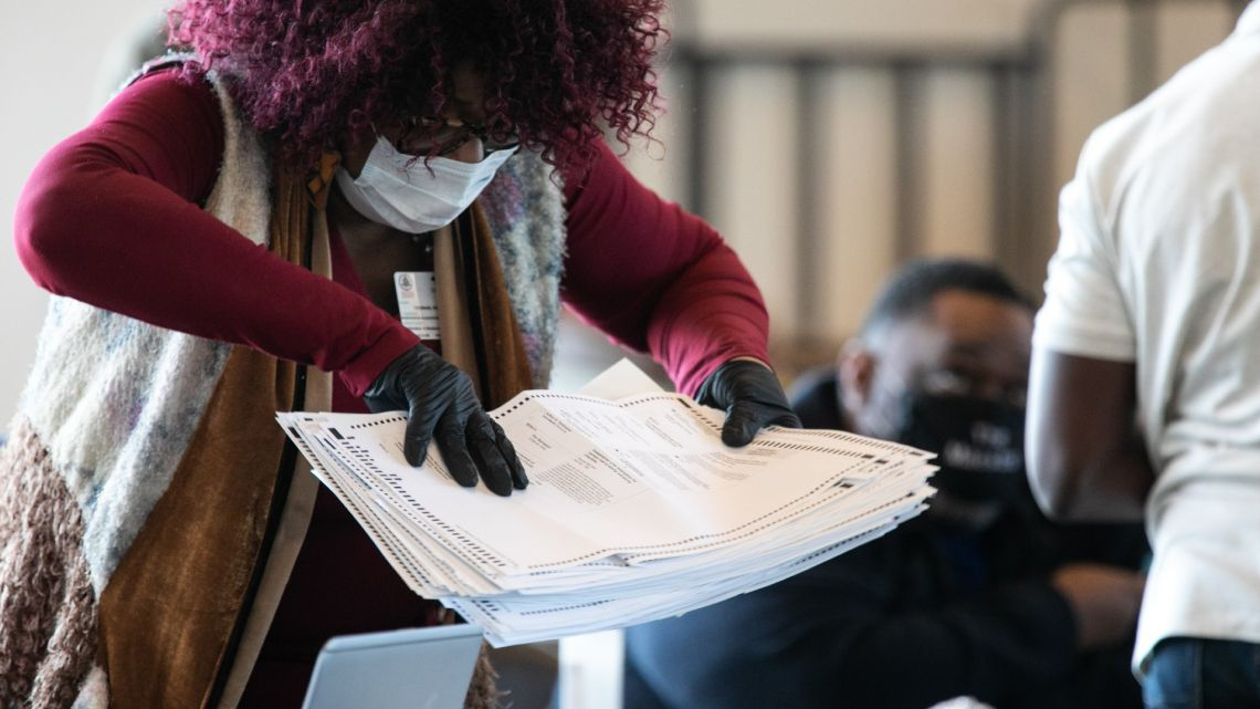A Fulton county worker moves a stack of absentee ballots at State Farm Arena on November 6, 2020 in Atlanta, Georgia.