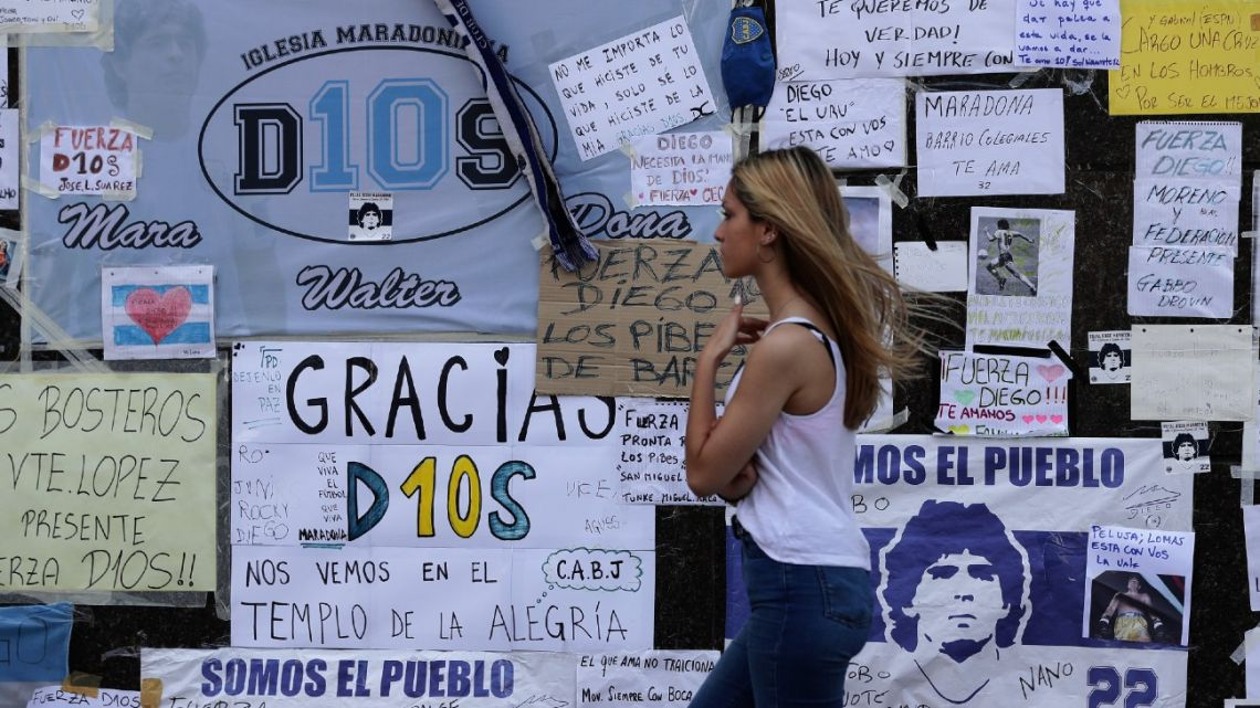 A woman walks by signs stuck up by fans of Diego Maradona on a wall outside the private clinic in Olivos where he underwent a brain surgery for a blood clot.