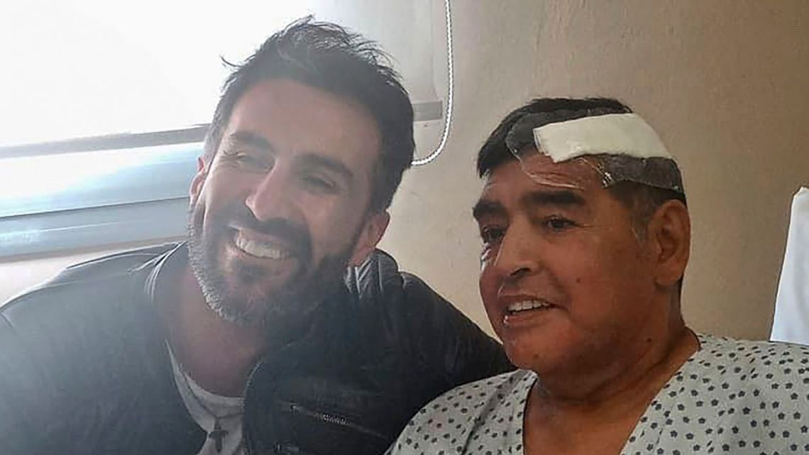 This handout photo released by the press officer for Diego Armando Maradona shows the Argentine football legend shaking hands with his doctor, Leopoldo Luque, at the Olivos clinic.