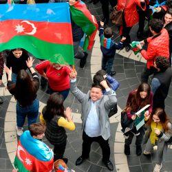 Los azerbaiyanos ondean la bandera nacional mientras celebran en las calles de la capital, Bakú, después de que Armenia y Azerbaiyán acordaron un alto el fuego tras una serie de victorias azeríes en la lucha por la disputada región de Nagorno-Karabaj.   Foto:Tofik Babeyev / AFP