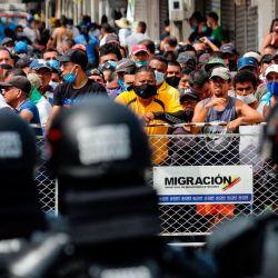 Dueños de comercios colombianos protestan frente a miembros del Escuadrón Móvil Antidisturbios de Colombia en el puente internacional La Unión en Puerto Santander, Colombia, en la frontera con Venezuela, en medio de la nueva pandemia de coronavirus.   Foto:Schneyder Mendoza / AFP