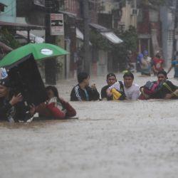 Los residentes cargan sus pertenencias mientras atraviesan una calle inundada para refugiarse después del paso del tifón Vamco, en la ciudad de Marikina, suburbana de Manila.   Foto:Ted Aljibe / AFP)