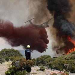 Los bomberos trabajan para extinguir un incendio mientras un avión bombardero acuático vuela cerca de Saint-Paul, en la isla francesa de La Reunión, en el Océano Índico.   Foto:Richard Bouhet / AFP