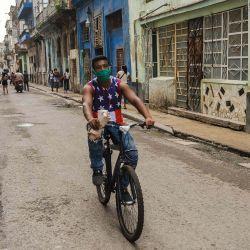 Un hombre vestido con una camiseta sin mangas con un diseño de la bandera de Estados Unidos y una mascarilla, viaja en su bicicleta por una calle de La Habana. | Foto:Yamil Lage / AFP