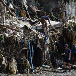 Los residentes caminan frente a su casa llena de escombros y basura en la ciudad de Marikina, en los suburbios de Manila, un día después de que el tifón Vamco azotara el área de la capital provocando fuertes lluvias e inundaciones. | Foto:Ted Aljibe / AFP)