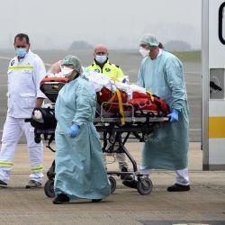 El personal médico del Lille SMUR atiende a un paciente de Covid-19 del hospital de Roubaix antes de un traslado en avión al hospital de Munster en el norte de Alemania, en el aeropuerto de Lille-Lesquin en Lesquin, norte de Francia. | Foto:FRANCOIS LO PRESTI / AFP