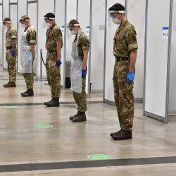 Los soldados guardan un silencio de 2 minutos por el día del Armisticio en recuerdo de las naciones muertas en la guerra en un centro de pruebas rápidas de coronavirus en el centro de exposiciones de Liverpool en Liverpool, noroeste de Inglaterra. | Foto:Paul Ellis / AFP
