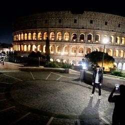 Las personas que usan máscaras protectoras toman fotografías frente al Coliseo en Roma, durante las medidas de restricción del gobierno para frenar la propagación de la pandemia Covid-19 causada por el nuevo coronavirus. | Foto:Filippo Monteforte / AFP