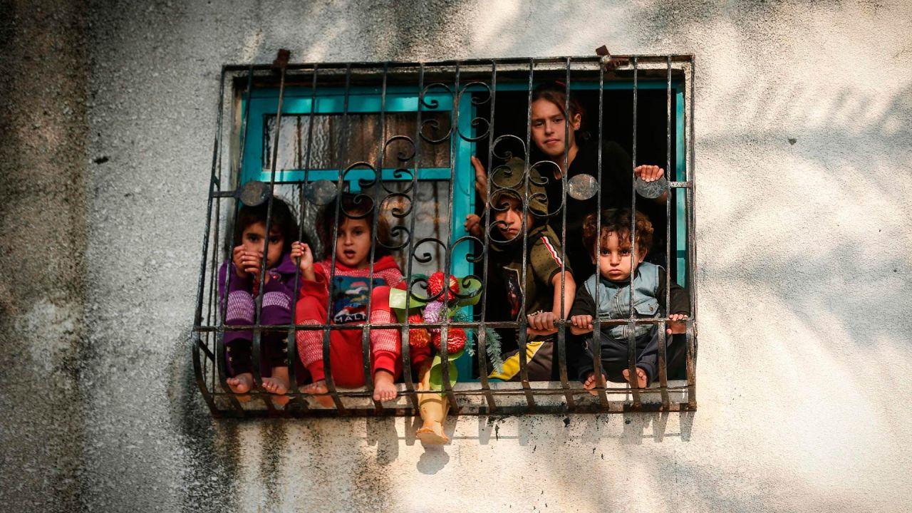 Los niños miran desde una ventana mientras los militantes palestinos de la Jihad Islámica participan en un mitin militar en la ciudad de Gaza para conmemorar el primer aniversario del asesinato del comandante del grupo, Baha Abu Al-Ata, en un ataque a su casa en el Franja de Gaza. | Foto:Mahmud Hams / AFP