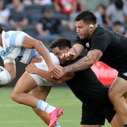 New Zealand's Anton Lienert-Brown (centre) and Tyrel Lomax (right) tackle Argentina's Santiago Carreras (left) during the 2020 Tri-Nations rugby match between the New Zealand and the Pumas at Bankwest Stadium in Sydney on November 14, 2020.