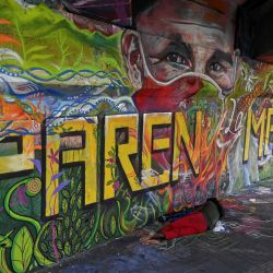 Una mujer camina frente a un mural que dice  | Foto:Luis Robayo / AFP