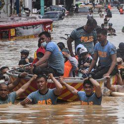 Los equipos de rescate tiran de un bote de goma que transportaba a los residentes a través de una calle inundada después del paso del tifón Vamco en la ciudad de Marikina, en los suburbios de Manila. | Foto:Ted Aljibe / AFP)
