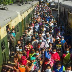 Los viajeros llegan a una estación de trenes suburbanos después de que el servicio de trenes se reanudara tras su cierre debido a la pandemia del coronavirus Covid-19 en Calcuta. | Foto:Dibyangshu Sarkar / AFP