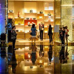 Los clientes esperan en la fila para ingresar a una tienda de lujo en un exclusivo centro comercial en Bangkok. | Foto:Mladen Antonov / AFP