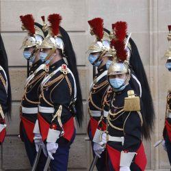Guardias republicanos franceses, con máscaras faciales, esperan la llegada del presidente senegalés al Palacio del Elíseo en París.   Foto:Ludovic Marin / AFP