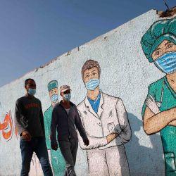Hombres palestinos pasan junto al arte callejero que muestra a los médicos con máscaras debido a la pandemia del coronavirus COVID-19, en Khan Yunis, en el sur de la Franja de Gaza.   Foto:Mohammed Abed / AFP