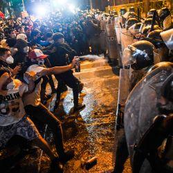 Manifestantes enfrentan a la policía antidisturbios durante una protesta contra el nuevo gobierno del presidente interino Manuel Merino, luego del juicio político y destitución del expresidente peruano Martín Vizcarra, en la plaza San Martín de Lima.   Foto:Ernesto Benavides / AFP