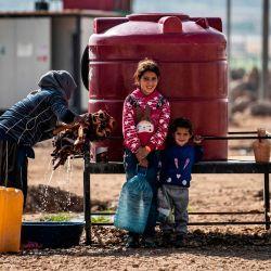 Una mujer y niños sirios, desplazados de Ras al-Ain, una ciudad fronteriza controlada por Turquía y sus representantes sirios, usan agua de un tanque en el campamento de Washokani en la gobernación de al-Hasakeh en el noreste de Siria.   Foto:Delil Souleiman / AFP