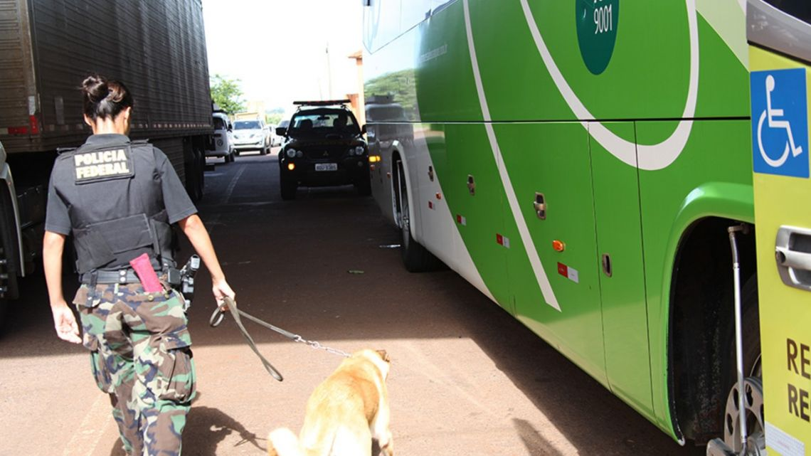 A PFA officer inspects a coach at the Argentina-Paraguay border crossing.