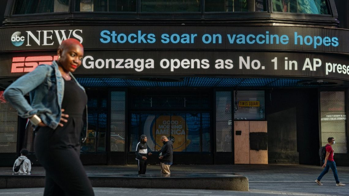 "An electronic billboard in Times Square announces ""stocks soar on vaccine hopes"" on November 9, 2020 in New York City."