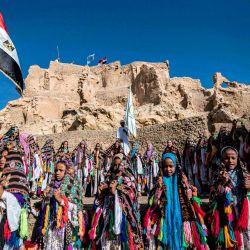 Escolares egipcios vestidos con trajes tradicionales, se reúnen durante una celebración para marcar la inauguración de la fortaleza de Shali después de su restauración, en el oasis del desierto egipcio de Siwa, a unos 600 kms al suroeste de la capital, El Cairo. | Foto:Khaled Desouki / AFP