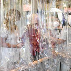 Un residente del asilo de ancianos Domenico Sartor recibe ayuda de enfermeras antes de hablar con un familiar a través de una pantalla de plástico en Castelfranco Veneto, cerca de Venecia, en una llamada  | Foto:Piero Cruciatti / AFP