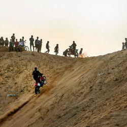 Los espectadores ven cómo un joven palestino sube en su motocicleta por una colina arenosa durante un espectáculo semanal en el área de Al-Zahra, cerca de la ciudad de Gaza. | Foto:Mahmud Hams / AFP
