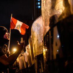 Manifestantes enfrentan a la policía antidisturbios durante una protesta contra el nuevo gobierno del presidente interino Manuel Merino, luego del juicio político y destitución del expresidente peruano Martín Vizcarra, en la plaza San Martín de Lima. | Foto:Ernesto Benavides / AFP