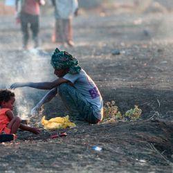 Migrantes etíopes que huyeron de intensos combates en su tierra natal de Tigray, cocinan su comida en el centro de recepción fronterizo de Hamdiyet, en el estado de Kasala, en el este de Sudán. | Foto:Ebrahim Hamid / AFP