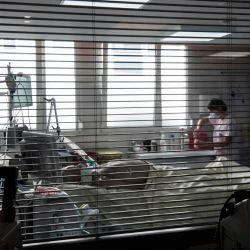 Un trabajador médico atiende a un paciente en una unidad de cuidados intensivos para pacientes infectados con el Covid-19 (nuevo coronavirus) en el hospital AP-HP Louis Mourier en Colombes, al noroeste de París. | Foto:ALAIN JOCARD / AFP