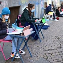 Anita Iacovelli y su amiga Lisa Rogliatti, ambas de 12 años, se sientan frente a la escuela Italo Calvino en Turín mientras protestan contra la no escuela desde el séptimo grado en adelante debido a las restricciones del gobierno sobre la pandemia Covid-19, causada por el nuevo coronavirus. | Foto:Miguel Medina / AFP