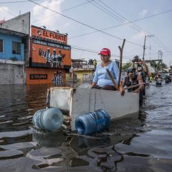 Un hombre empuja a un anciano sentado en un armario de madera en una calle inundada después de que las fuertes lluvias azotaran el estado de Tabasco. | Foto:Foto: German Espinosa / DPA
