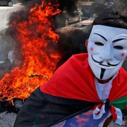 Un hombre que lleva una máscara de Guy Falkes aparece mientras los partidarios del movimiento palestino Fatah marchan para conmemorar el 16 aniversario de su muerte en la aldea de Dura, cerca de la ciudad cisjordana de Hebrón. | Foto:Hazem Bader / AFP