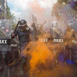 El humo naranja de una granada de humo envuelve a una fila de policías que intentan dispersar a los manifestantes a favor de la democracia durante una manifestación antigubernamental cerca del Parlamento tailandés en Bangkok. | Foto:Cory Wright / AFP