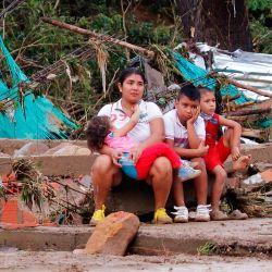 Una mujer y niños se sientan junto a su casa destruida después de que las fuertes lluvias causaron destrucción en Cúcuta, Colombia. | Foto:Schneyder Mendoza / AFP