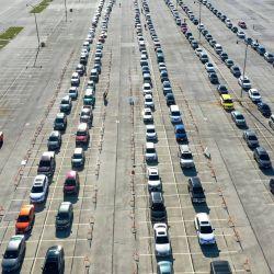 Una imagen aérea tomada con un dron muestra a los residentes alineados en sus autos en un centro de pruebas COVID-19 en los terrenos de Miller Park en Milwaukee, Wisconsin. Wisconsin informó recientemente una tasa de positividad de COVID-19 promedio de siete días de casi el 40%. | Foto:Scott Olson / Getty Images / AFP