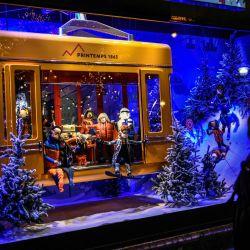 Una mujer mira uno de los escaparates navideños recién revelados de la tienda Printemps Haussmann en París. | Foto:STEPHANE DE SAKUTIN / AFP