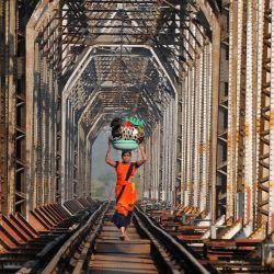 India, Mumbai: una mujer lleva equipaje mientras camina por las vías del tren. | Foto:Ashish Vaishnav / DPA