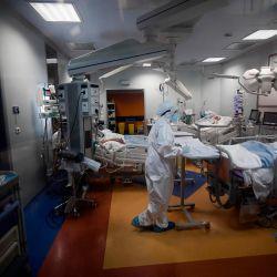 Una enfermera escribe notas mientras los pacientes yacen en la cama en la Unidad de Cuidados Intensivos para pacientes con COVID-19 en el Instituto Clínico Casalpalocco en Roma, durante la pandemia causada por el nuevo coronavirus. | Foto:Filippo Monteforte / AFP)