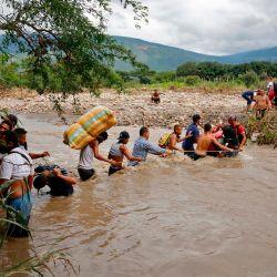 Los migrantes utilizan una cuerda para cruzar el río Táchira, la frontera natural entre Colombia y Venezuela, ya que la frontera oficial permanece cerrada debido a la pandemia de COVID-19 en Cúcuta, Colombia. | Foto:Schneyder Mendoza / AFP