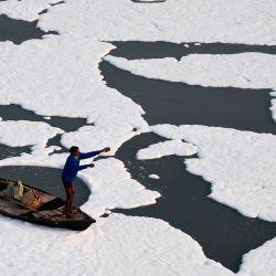 Hombres remando un bote en las aguas contaminadas del río Yamuna cubiertos de espuma en Nueva Delhi. | Foto:Sajjad Hussain / AFP