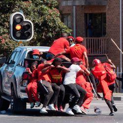 Los miembros de los Economic Freedom Fighters (EFF) suben a un camión para huir mientras la policía dispara balas de goma para dispersarlos durante una manifestación contra el presunto racismo cerca de la escuela secundaria Brackenfell, donde supuestamente se organizó una fiesta de baile de fin de año solo para blancos el mes pasado. en Ciudad del Cabo. | Foto:RODGER BOSCH / AFP