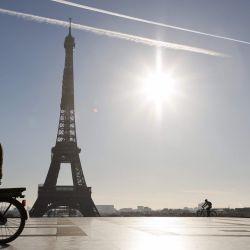 Un hombre monta una bicicleta eléctrica frente a la Torre Eiffel, en la plaza Trocadero de París, durante un segundo bloqueo en Francia destinado a contener la propagación de la pandemia Covid-19, causada por el nuevo coronavirus.   Foto:Ludovic Marin / AFP