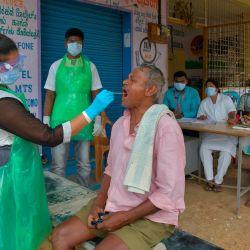 Un funcionario de salud toma una muestra de un hisopo de un hombre para realizar la prueba del coronavirus Covid-19 en una aldea en las afueras de Bangalore.   Foto:Manjunath Kiran / AFP