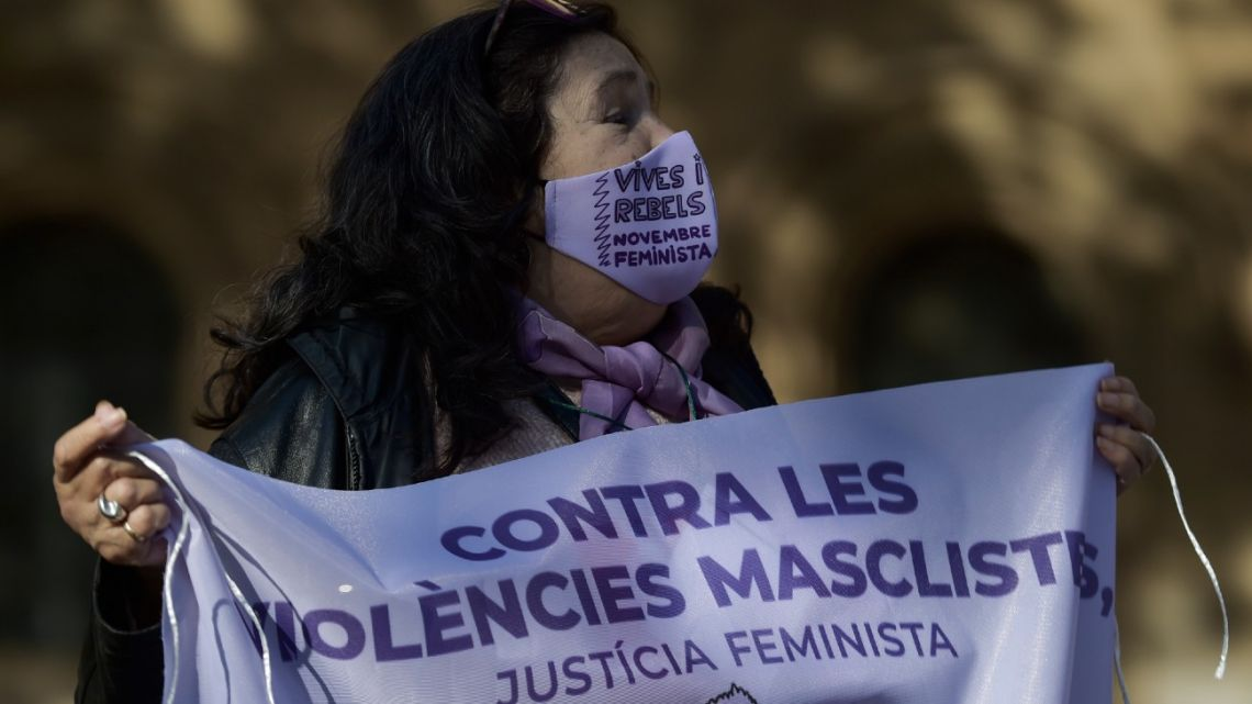 "A woman wearing a face mask reading ""Alive and rebels"" holds a banner reading ""Against gender violence, feminist justice"" during a protest called by feminist associations in Barcelona on November 22, 2020, ahead of November 25 which marks the International Day for the Elimination of Violence against Women."