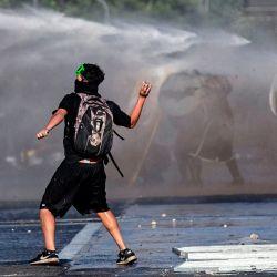 Un manifestante lanza una piedra a la policía antidisturbios mientras sus compañeros manifestantes son rociados por un cañón de agua durante los enfrentamientos tras una protesta contra el gobierno del presidente chileno Sebastián Piñera en Santiago. | Foto:Javier Torres / AFP