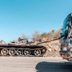 Un tanque dañado está abandonado en una carretera cuando un camión de las Fuerzas Especiales de Amhara pasa cerca de Humera, Etiopía. | Foto:AFP