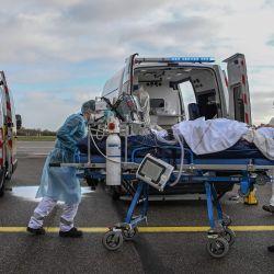 Personal médico transporta a un paciente en camilla a un vuelo médico en espera, para ser evacuado a otro hospital, en el aeropuerto de Bron cerca de Lyon, sureste de Francia, en medio del brote del Covid-19 provocado por el nuevo Coronavirus. | Foto:Philippe Desmazes / POOL / AFP