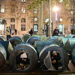 Migrantes y asociaciones instalan tiendas de campaña en la plaza de la República en París, una semana después de que los migrantes fueran evacuados de un campamento improvisado en el popular suburbio de Saint-Denis, en el norte de París, sin ser reubicados. | Foto:Martin Bureau / AFP