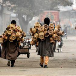 Los vendedores llevan Kangri (vasijas de barro cubiertas con mimbre que se utilizan para mantener a la gente caliente) durante un día brumoso en Srinagar. | Foto:Tauseef Mustafa / AFP